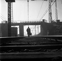 Dans les environs de Toulouse. Le 23 Octobre 1963. Vue d'un voyageur avec sa valise marchant seul sur la voie ferrée dans les environs de Toulouse.