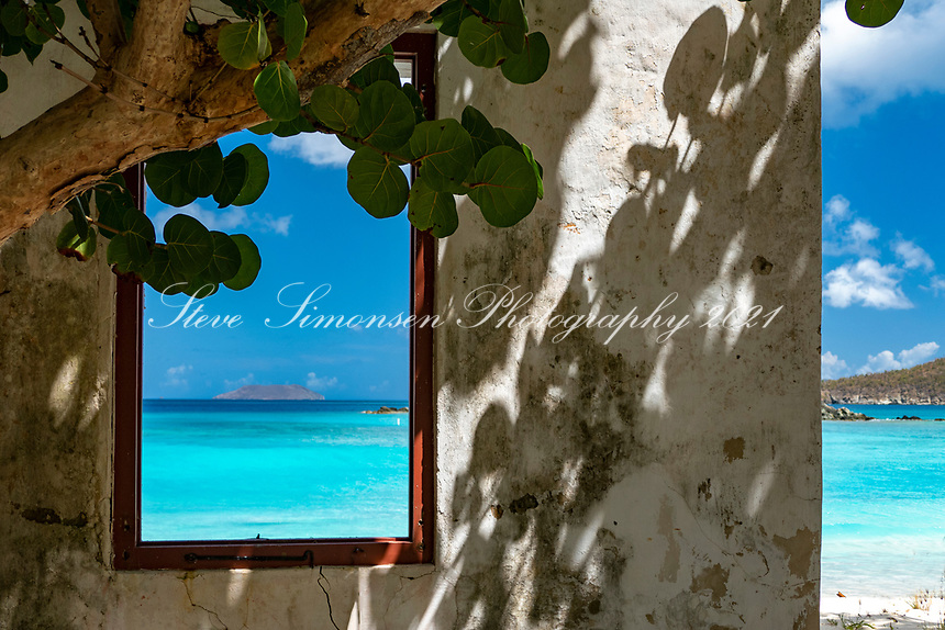 Ruins of the old museum structure at Cinnamon Bay with a view of the turquoise water through the window<br /> Virgin Islands National Park<br /> St. Joh<br /> US Virgin Islands