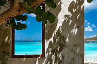 Ruins of the old museum structure at Cinnamon Bay with a view of the turquoise water through the window<br />