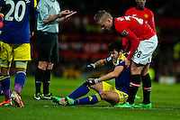 Sunday 05 January 2014<br /> Pictured:Alejandro Pozuelo lies on the floor injured as Alexander B?ttner tries to lift him <br /> Re: Manchester Utd FC v Swansea City FA cup third round match at Old Trafford, Manchester