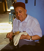 Tunisian Hat, Chechia.  Chechia Vendor Abdelkader El-Jaoui Combing an Undyed Chechia with a Thistle-Comb to remove excess wool.