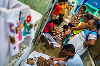 """Mayan peasants clean dried-up bones of deceased family members during the bone cleansing ritual at the cemetery in Pomuch, Mexico, 26 October 2019. Every year on the Day of the Dead, people of Pomuch, a small Mayan community in the south of Mexico, visit the cemetery to take part in a pre-Hispanic tradition of cleaning of bones of their departed relatives (""""Limpia de huesos""""). People who die in Pomuch are firstly buried for three years in an above-ground tomb then the dried-up bodies are taken out, bones are separated, wrapped in a decorated cloth, put into a wooden crate, and placed on display among flowers for veneration."""