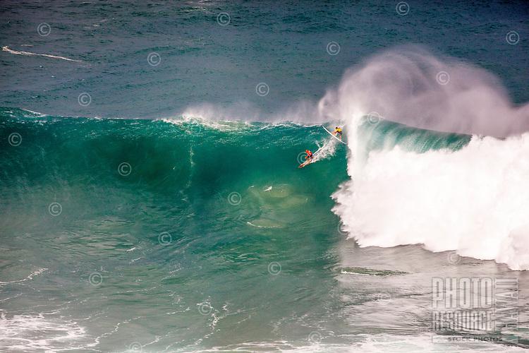 Surfers ride a wave at the 2016 Big Wave Eddie Aikau Contest, Waimea Bay, North Shore, O'ahu.