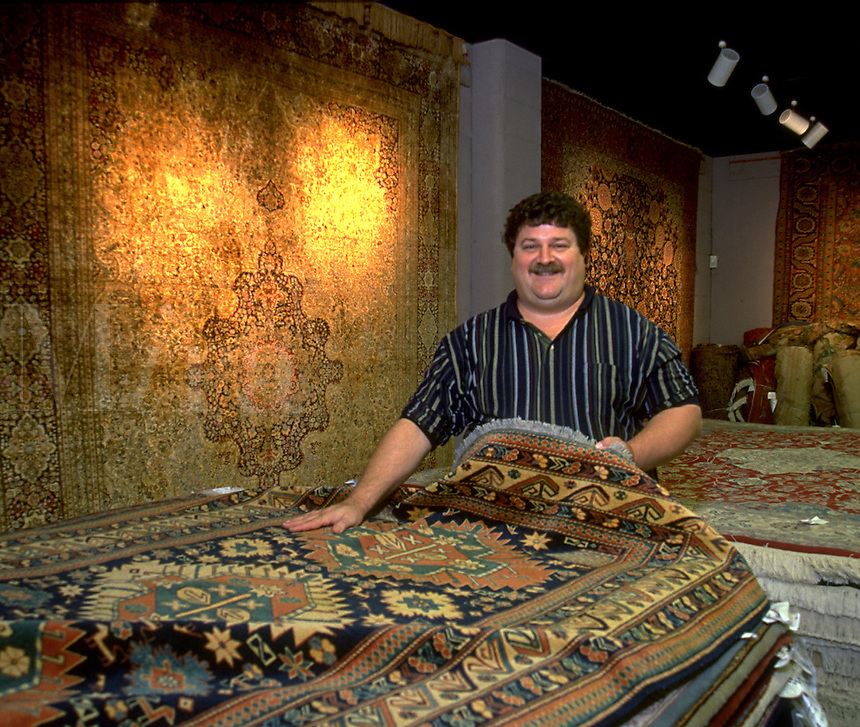 A smiling store owner displays an oriental rug in a showroom.