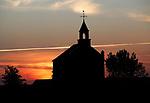 Foto: VidiPhoto<br /> <br /> HOMOET – De zon zakt weg achter het beeldbepalende waterstaatskerkje in het buurtschap Homoet in de Betuwe. Een mooi sfeervol beeld. Echter... de kleine buurtkerk wordt in verband met de coronacrisis al enkele maanden niet meer gebruikt en vermoedelijk zal dat voorlopig ook wel zo blijven. Het eigendom van de Hervormde gemeente Valburg-Homoet is te klein om vanaf 1 juni met de dertig toegestane kerkgangers, de verplichte 1,5 meter afstand te kunnen waarborgen. Bovendien heeft het gebouw geen stromend water en alleen een chemisch toilet. De Hervormde gemeente heeft daarom besloten om alleen de grotere kerk in Valburg te gebruiken voor de erediensten. Het kerkje in Homoet telt slechts zestig vaste zitplaatsen en is een van de kleinste kerkjes van ons land.