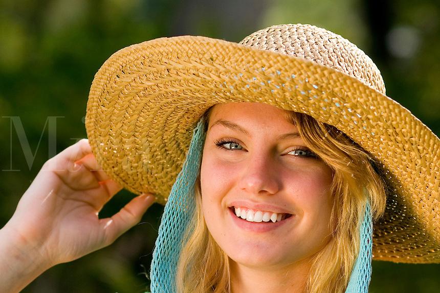 Teenage girl having fun with a hat.