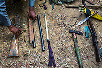 After photo-documentation, police confiscates the weapons used by two arrested poachers who killed and skinned a wild elephant in the forest reserve area in Thar Paung.