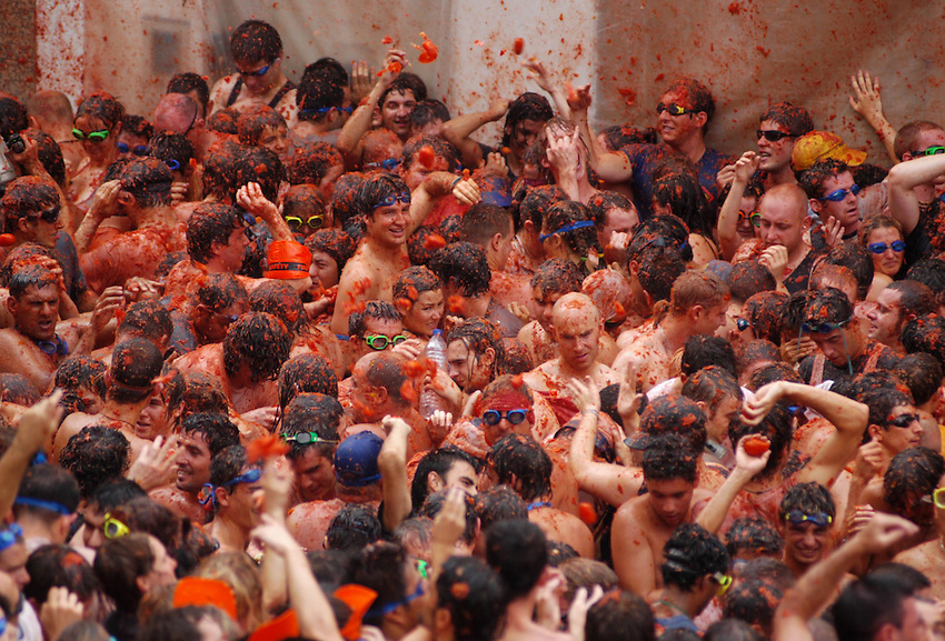 BUNYOL, SPAIN - AUGUST 31: People fighting during the Tomatina August 31, 2005 in Bunyol, Valencia, Spain. Approximately 45,000 people pelted each other with a little over 100.000 kilograms of tomatoes. The tomatina is known as the world's largest tomato battle. Photo by Ander Gillenea