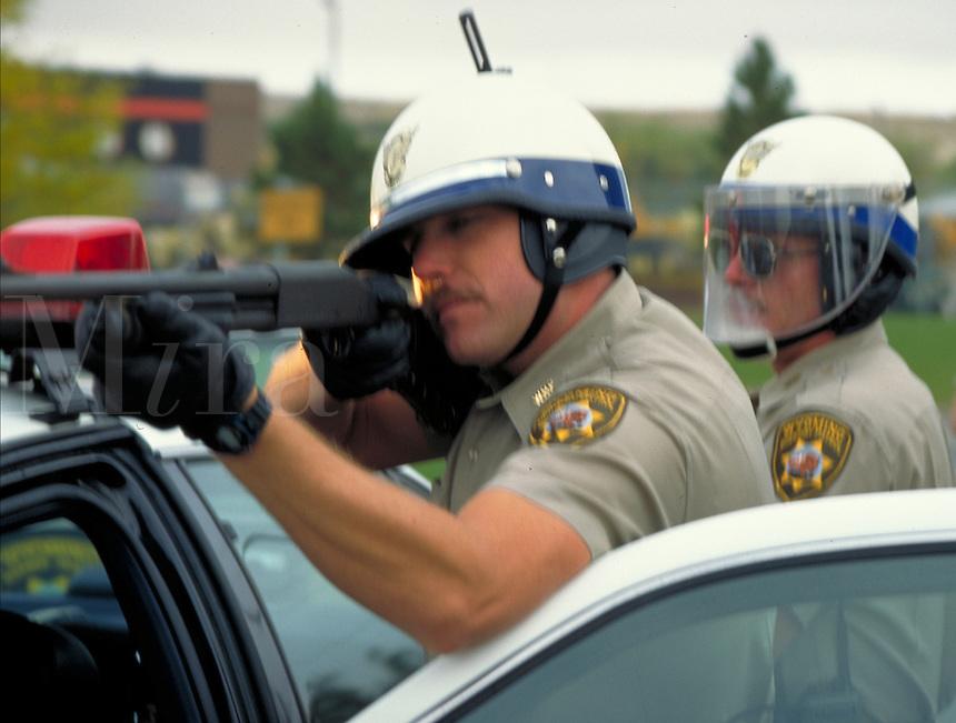 Wyoming Highway Patrolmen in riot gear take aim with a shotgun, artillery, cops, police officers. Casper Wyoming USA.