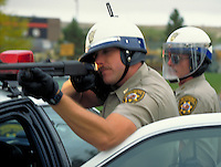 Wyoming Highway Patrolmen in riot gear take aim with a shotgun, artillery, cops, police officers. Casper Wyoming USA.