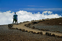 Man and woman standing on the edge of the mountain looking down upon the clouds in HALEAKALA NATIONAL PARK on Maui in Hawaii USA