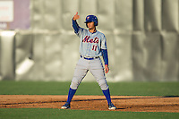 Dionis Rodriguez (11) of the Kingsport Mets shades his eyes from the sun as he takes his lead off of first base during the game against the Danville Braves at American Legion Post 325 Field on July 9, 2016 in Danville, Virginia.  The Mets defeated the Braves 10-8.  (Brian Westerholt/Four Seam Images)