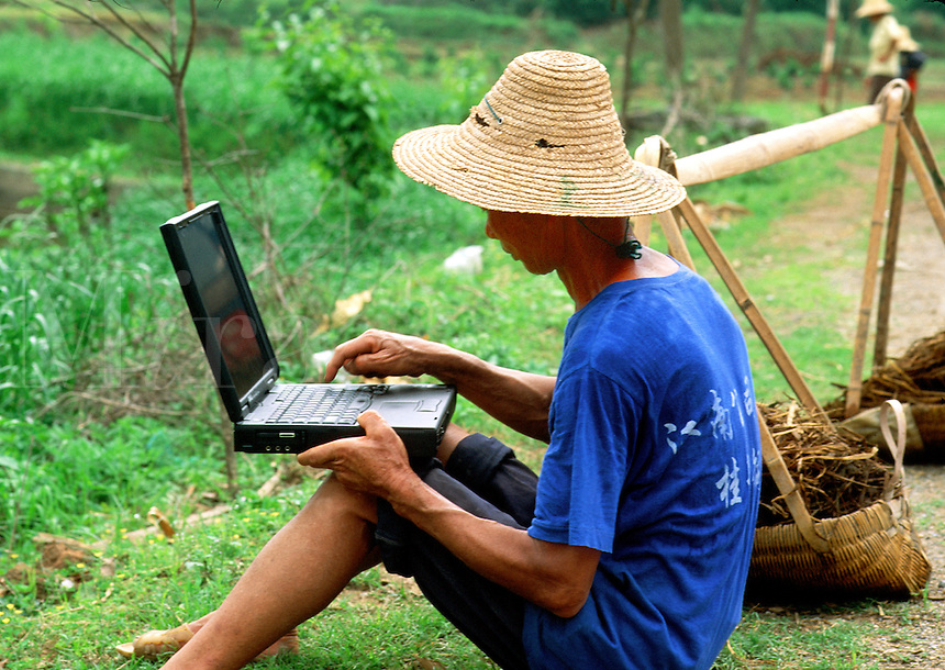 A Chinese farmer in a straw hat uses a laptop computer to connect to the internet while in the fields. Guilin, China.