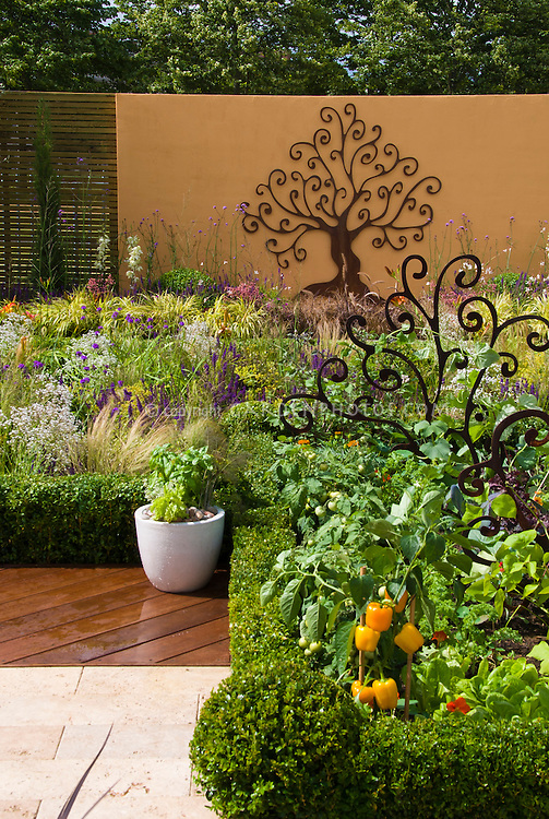 Rustic tree garden ornament on wall and in vegetable garden next to patio deck, with flower beds, Buxus boxwood edging hedge