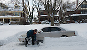 A car owner digs out their car after a snow plow went by after a winter storm.
