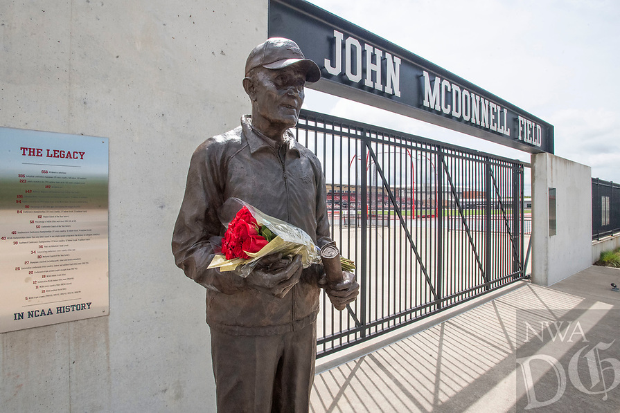 A bouquet rests in the hands of the John McDonnell statue Tuesday June 8, 2021 at John McDonnell Field at the University of Arkansas in Fayetteville. McDonnell  died Monday at age 82. He led the University of Arkansas men's cross country and track and field teams into to 40 national championships, 19 in indoor track and field, 11 in cross country and 10 in outdoor track and field, between 1984 and 2006.  Visit nwaonline.com/2100609Daily/ and nwadg.com/photo. (NWA Democrat-Gazette/J.T. Wampler)