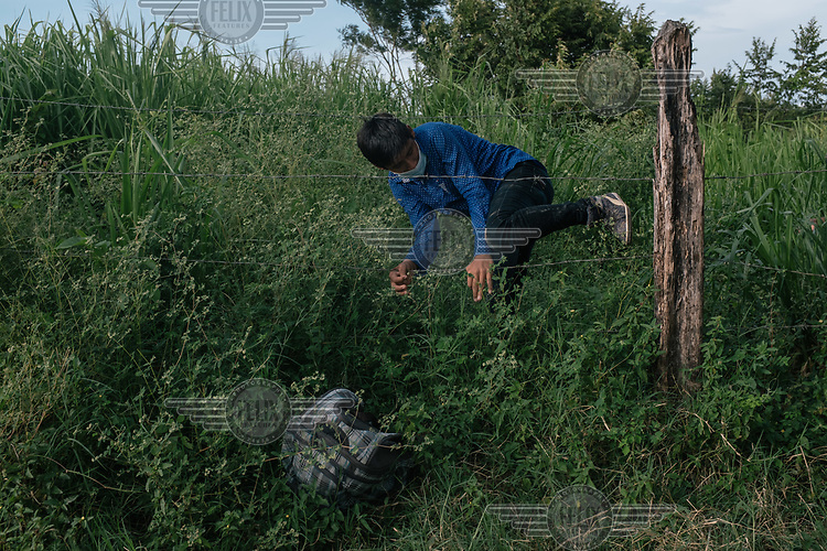A central American migrant climbs through a fence on the border near the official El Ceibo port of entry between Guatemala and Mexico.