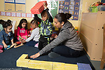 Education Preschool classroom scenes 2s program female teacher working with boy playing with cardboard blocks as girl in background play with train set