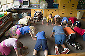 MR / Schenectady, NY. Zoller Elementary School (urban public school). Kindergarten inclusion classroom. Teacher does yoga with students to get them to settle down.  MR: War15. ID: AM-gKw. © Ellen B. Senisi.
