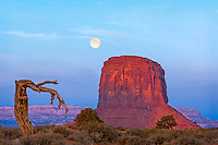 The moon sets behind one of the buttes in Monument Valley Utah.