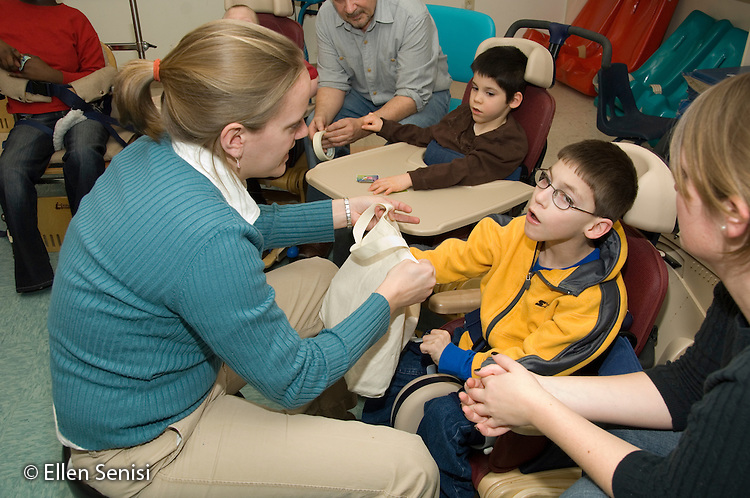 MR / Albany, NY.Langan School at Center for Disability Services .Ungraded private school which serves individuals with multiple disabilities.Child reaches for a letter in an alphabet bag the teacher holds while others watch during language arts lesson. He is sitting in Rifton chair. Boy: 9, cerebral palsy, limited verbal output with expressive and receptive language delays.MR: AH-cfds.© Ellen B. Senisi