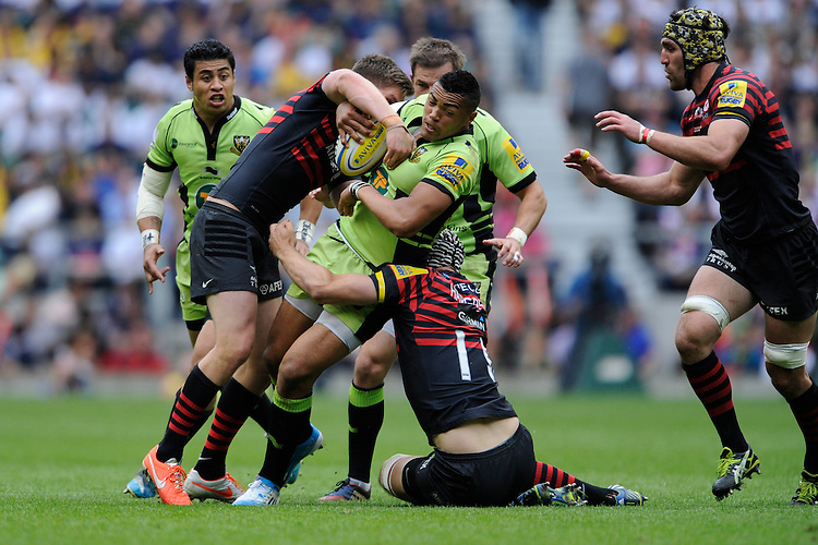 Luther Burrell of Northampton Saints is tackled by Owen Farrell and Kelly Brown of Saracens during the Aviva Premiership Final between Saracens and Northampton Saints at Twickenham Stadium on Saturday 31st May 2014 (Photo by Rob Munro)