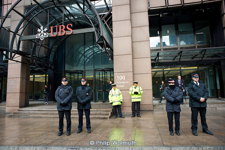 Security guards and City of London police outside the London headquarters of Swiss bank UBS, during a rally in support of Alberto Durango, a member of UNITE and the Latin American Workers Association, a cleaner sacked by contractor Lancaster Cleaning and Support Services following a campaign for improved pay and conditions.