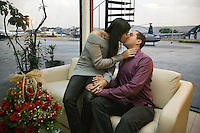 A young couple enjoy each other's company in a VIP room. They are about to depart on a night tour flying over Sao Paulo for 17 minutes, landing on Sofitel's helipad. They will then have a special dinner and a romantic night at the hotel. This service, called Night Air is one of the many types of helicopter use becoming increasingly popular in Sao Paulo. .