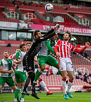 5th April 2021; Bet365 Stadium, Stoke, Staffordshire, England; English Football League Championship Football, Stoke City versus Millwall; Goalkeeper Bartosz Bialkowski of Millwall thumps the ball clear under pressure from Nick Powell of Stoke City