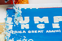 People cut slices of a birthday cake decorated like a 2020 Trump campaign sign for former 2016 Trump campaign manager and current 2020 Trump campaign senior advisor Corey Lewandowski  is seen as people gather for a Trump campaign office opening party in Salem, New Hampshire, on Fri., Sept. 18, 2020. Lewandowski lives in nearby Windham, NH, and attended the party to speak about the ongoing campaign.