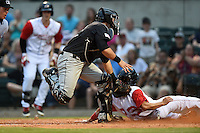 San Antonio Missions catcher Austin Hedges (15) tags out Vance Albitz (23) sliding into home during a game against the Arkansas Travelers on May 24, 2014 at Dickey-Stephens Park in Little Rock, Arkansas.  Arkansas defeated San Antonio 4-2.  (Mike Janes/Four Seam Images)