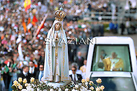 Officials (unseen) carry a Virgin of Fatima statue as Pope Benedict XVI arrives in his Popemobile to lead the traditional annual mass at Fatima's Sanctuary in Portugal on May 13, 2010. The mass marked the anniversary of the day in 1917 when three shepherd children reported to have seen the first of a series of apparitions of the Virgin Mary, turning the Portuguese village into one of the biggest draws for the Roman Catholic faithful