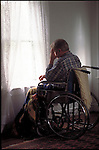 disabled man in wheelchair looking out window of room