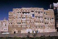 Old mud construction tall townhouse dwelling, in the modern city, grassy vacant lot in the forefront, architecture. Yemen.