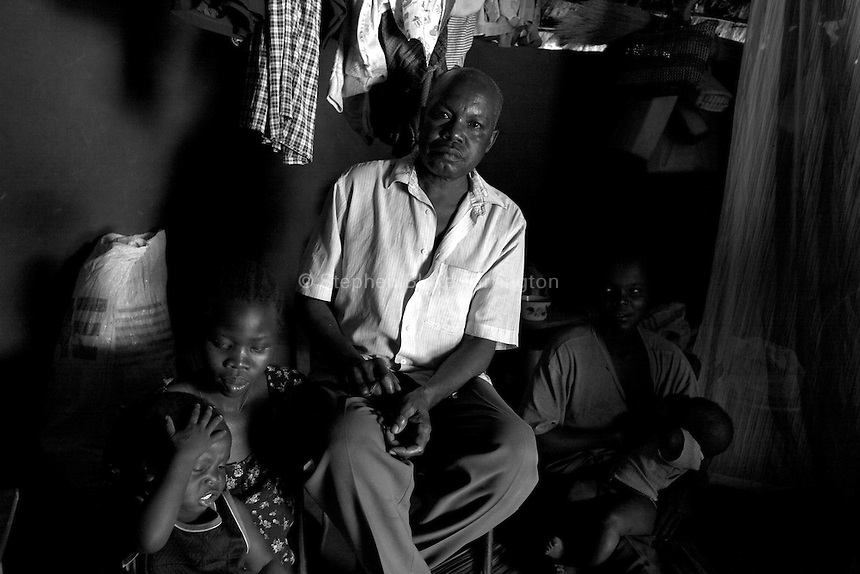 This local leader poses with his two daughters inside of his dwelling at Unyama Internally Displaced PeopleÕs (IDPs) camp. The IDP camps of Northern Uganda formed when areas in the region became unsafe for civilians to live. Clean water, sanitation, food, employment, education, moral living, and human rights have almost been entirely depleted. Furthermore, congestion within the camps has contributed to major health and living problems. With 1.6 Ð 2 million people displaced and with an almost total lack of resources to care for them, the local peopleÕs very existence physically, emotionally and culturally is at stake. The war between the LordÕs Resistance Army and the Ugandan military has been transpiring since 1986. Thousands have been killed and abducted. Unyama (off Kitgum Road North) Gulu District, Uganda, Africa. December 2005 © Stephen Blake Farrington
