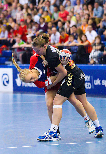 30 MAY 2012 - LONDON, GBR - Nina Heglund (GBR) of Great Britain (left, in red and blue) finds her path to goal blocked by Suzana Lazovic (MNE) of Montenegro (right, in black and gold) during the women's 2012 European Handball Championship qualification match at the National Sports Centre in Crystal Palace, Great Britain .(PHOTO (C) 2012 NIGEL FARROW)