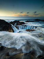 At sunset, water rushes towards a hole in the Keahole Point shoreline on the Big Island.