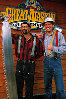 Two smiling male lumberjacks pose with a saw and an axe. Alaska.
