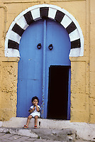 Tunisia, Sidi Bou Said.  Little Girl Sitting by her Door.  The high door knockers date from a time when guests arrived on horseback.