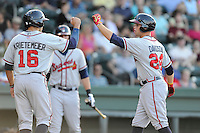 Right fielder Braxton Davidson (24) of the Rome Braves, right, is congratulated by Tanner Krietemeier (16) after scoring a run in a game against the Greenville Drive on Friday, June 12, 2015, at Fluor Field at the West End in Greenville, South Carolina. Greenville won, 10-8. (Tom Priddy/Four Seam Images)