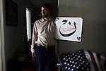 """Adam Warshauer, 37, from Delray Beach, FL, whose father is Jewish and mother is a Christian, became a Sufi Muslim after being introduced to the faith by a man he met at 22. He is seen here posing for a portrait with a passage from the Surat Al-Qalam in the Koran, in a just-moved-into office space in Delray Beach, on March 12, 2016. <br /> <br /> He credits his background for being able to see connections between the three religions, and plans to start a YouTube show directly addressed to U.S. Presidential candidate Donald Trump (R-NY,) with the aim of creating """"peace between the Israel and Arab nations."""" It would feature a hand puppet called Uncle Musa - a relative to Moses, a prophet who appears in the Torah, Bible and Koran.<br /> <br /> Politically, he says he identifies most as an Independent: """"I believe in protecting the environment, and Republicans don't, which is why I am not Republican."""" Warshauer plans to support Trump, however, especially if he wins Tuesday's primary elections and goes on to become the Republican nominee for president. <br /> <br /> Warshauer says he does not believe Trump wants to ban Muslims from entering the country because of a dislike for them, but because he wants to solve terrorism.""""Most are outraged at Trump saying he wants to ban Muslims from entering America, but I support that as a Muslim person, because we have to stop what is happening and work with other Muslim countries to stop terrorism. If you stop Muslims from entering the country, it forces everyone to look at the problem."""" He adds that """"Isis killings are ruining the face of Islam. Who wants to become Muslim when it is associated with terrorism?""""<br /> <br /> """"People pull stuff they want to go """"Oh, my God!"""" about, but come on, forget about that and just focus on what's real,"""" which Warshauer says is Trump's job creation capability and his focus on stopping the drug epidemic in America, heroin specifically. He adds that Trump is more approachable than other Republican can"""
