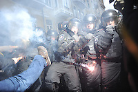 A protester kicks riot police (Bekrut) while others light smoke candles.  <br /> <br /> The protesters storm the Kiev city council building, venting their anger over the Ukrainian  government's decision to stall on a deal that would bring closer ties with the European Union.