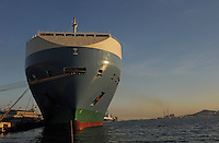 A massive ship parks on the port next to a car transporter in Ulsan South Korea. The Ulsan plant is the world's largest automobile plant which has its own port where up to three, 50,000-ton ships can anchor simultaneously..