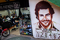 "A portrait artwork, depicting the drug lord Pablo Escobar, is seen painted on the wall next to a barber shop in the Pablo Escobar neighborhood in Medellín, Colombia, 30 November 2017. Twenty five years after Pablo Escobar's death, the legacy of the Medellín Cartel leader is alive and flourishing. Although many Colombians who lived through the decades of drug wars, assassinations, kidnappings, reject Pablo Escobar's cult and his celebrity status, there is a significant number of Colombians who admire him, worshipping the questionable ""Robin Hood"" image he had. Moreover, in the recent years, the popular ""Narcos"" TV series has inspired thousands of tourists to visit Medellín, creating a booming business for many but causing a controversial rise of narco-tourism."