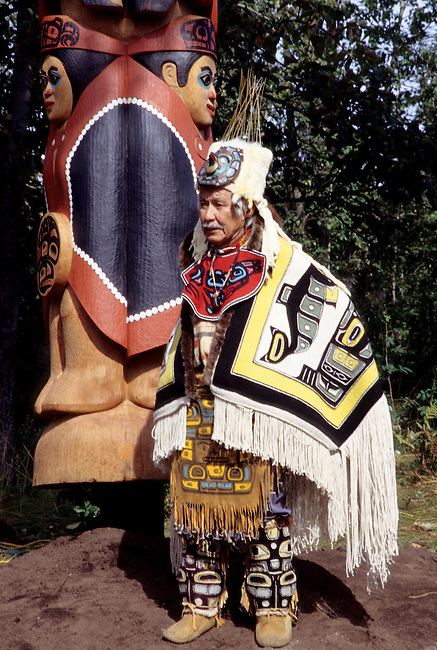 Tlingit master carver, Nathan Jackson, dressed in traditional regalia and chilkat blanket stands in front of his latest carved totem pole during a raising ceremony. Model released