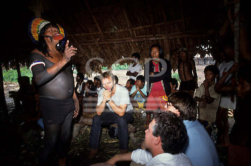 Amazon, Brazil. Sting with face paint, Larry Cox listening to Chief Raoni; men's hut, Capoto village, Megranoti Reserve.
