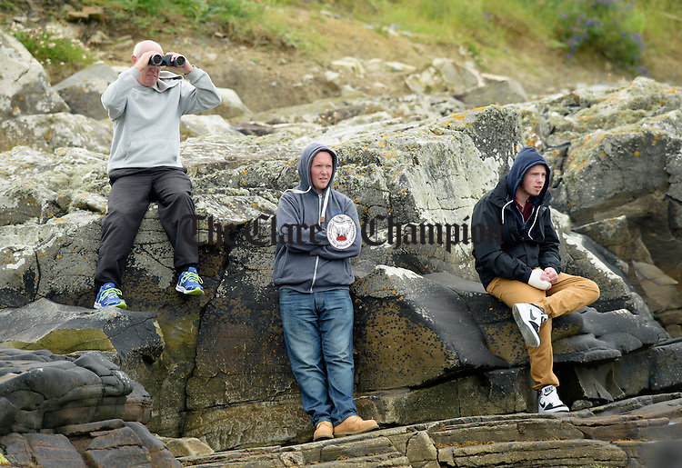 Spectators Jimmy Mc Donagh and his sons Stephen and Michael of Connemara watch all the action from the shore during the All-Ireland  Currach Regatta at Doonbeg. Photograph by John Kelly.