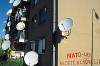 Kosovo. Pristina. Daily life. Man on the balcony. On most balconies are television parabol antennas for better tv reception and a wide diversity of programms. Nato and UCK (kosovo liberation army) graffiti on the wall. © 2001 Didier Ruef