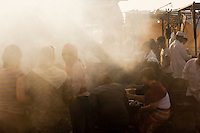 People crowd around to eat food at a stall in the Djemaa el Fna in the medina of Marrakech, Morocco. Every night the main square fills with dozens of food vendors and their carts.