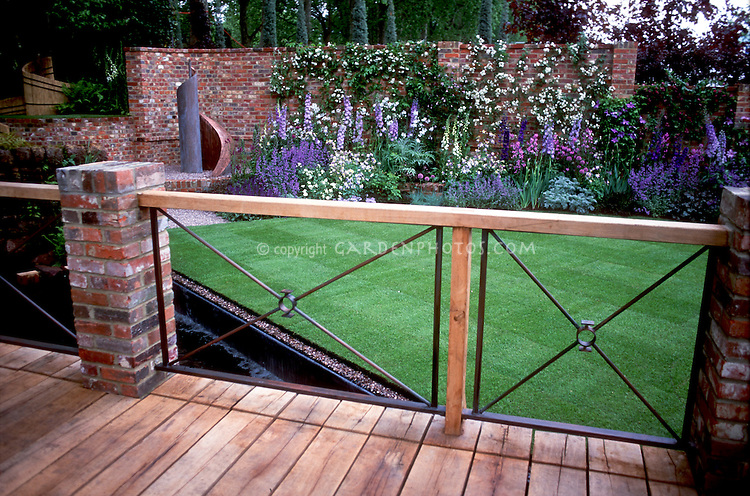 Deck landscaping view looking over glorious upscale garden with lots of flowers and plants in blue and purple color theme, brick wall with climbing vines, in mathematical proportions Design: Xa Tollemache & Jon Kellett